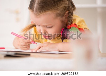Closeup portrait of little beautiful kid, cute girl painting with marker ink pen, pens and paints on the desk, interior shot - stock photo