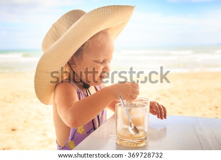 closeup portrait of little blond cute girl in large straw hat drinking juice with tea spoon from glass at table on beach - stock photo