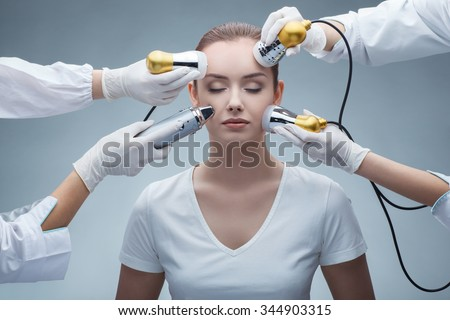 closeup portrait of lovely calm young woman with hands holding medical maniples touching her face