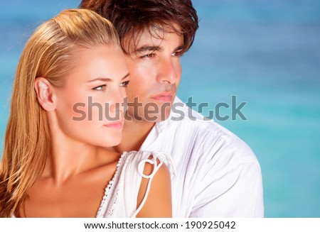 Closeup portrait of lovely couple looking in side on blue sea background, boyfriend and girlfriend enjoying summer vacation - stock photo