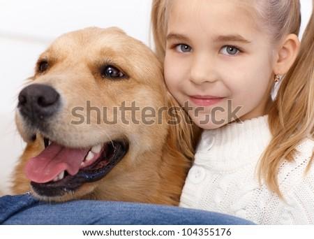 Closeup portrait of lovely little girl and golden retriever, hugging, smiling. - stock photo