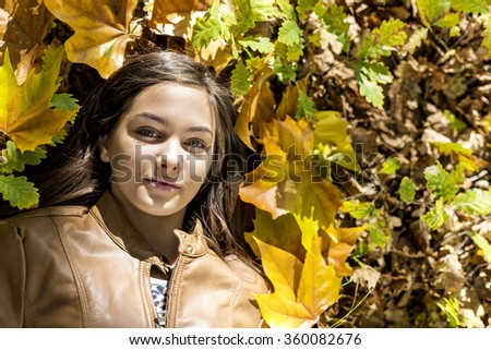 Closeup portrait of  lovely teenage girl lying on autumn fallen leaves in the forest - stock photo