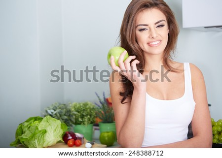 Closeup portrait of lovely young brunette woman biting juicy fresh delicious apple against gray background. Beautiful young lady eating healthy food.