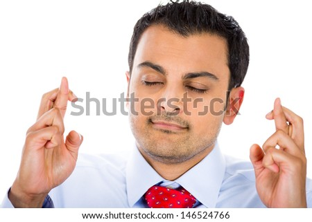 Closeup portrait of man with blue shirt and red tie crossing fingers, wishing and dreaming for something, isolated on white background with copy space - stock photo