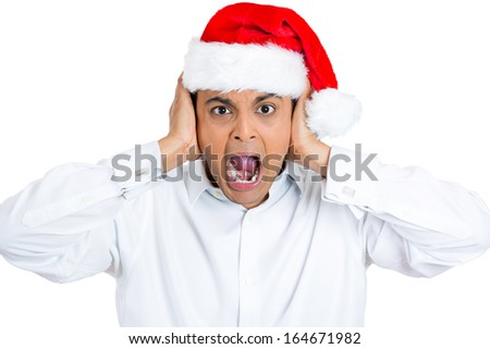 Closeup portrait of mean young man in red santa claus hat covering closing ears with hands to block loud noise, yelling isolated on white background with space to left. Human emotion facial expression