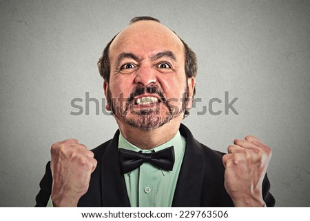Closeup portrait of middle aged angry man on grey background   - stock photo