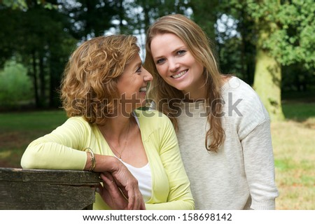 Closeup portrait of mother and daughter smiling outdoors