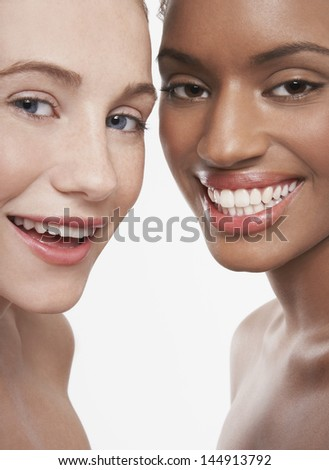 Closeup portrait of multiethnic young women smiling isolated on white background - stock photo