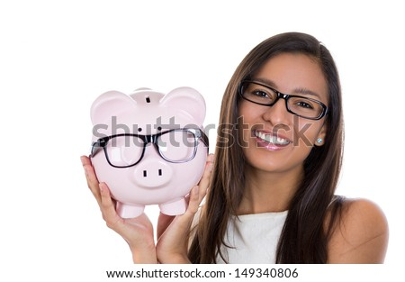 Closeup portrait of nerdy young woman holding piggy bank, both with big black glasses, isolated on white background. Positive emotion facial expression feelings. Smart wise financial decision savings