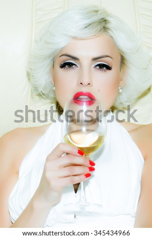 Closeup portrait of one attractive sensual smiling sexy young retro woman with blonde hair red lips in white dress in monroe style indoor drinking glass of wine, vertical picture - stock photo