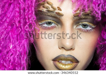 Closeup portrait of one beautiful wild young woman with bright golden animal monkey makeup with thorns on face in fur violet wig in studio, horizontal picture