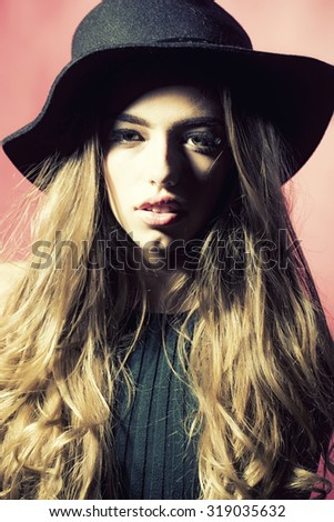 Closeup portrait of one fashionable young attractive sensual female model with lush long blonde curly hair in black shady hat looking forward in studio on pink background, vertical picture - stock photo