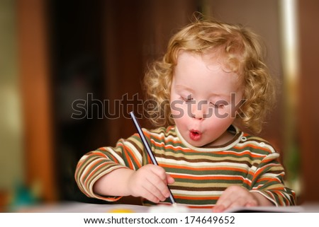 Closeup portrait of preschooler with strawberry blonde curly hairs who draws in the sketchbook by pencil, looks down and sing