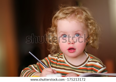 Closeup portrait of preschooler with strawberry blonde curly hairs who draws in the sketchbook by pencil and looks up - stock photo