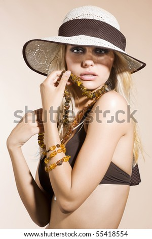 closeup portrait of pretty blond woman wearing a nice summer hat and natural jewellery - stock photo