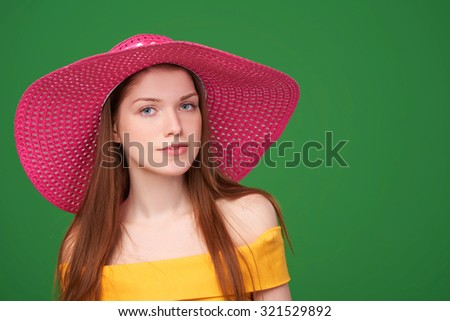 Closeup portrait of pretty girl in yellow strapless summer dress and wide-brimmed straw hat posing in studio over green background.