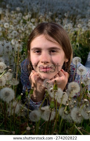 Closeup Portrait of Pretty Girl With Freckles Sprinkled Across Her Nose Leaning Her Chin on Hands and Resting on Dandelion Field on Sunny Spring Day - stock photo