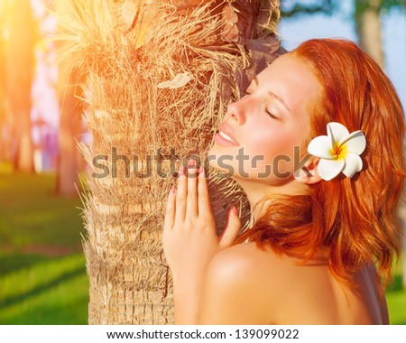 Closeup portrait of pretty redhead woman with frangipani flower in hair and closed eyes enjoying warm sun light, luxury tropical resort, summer time vacation and holidays