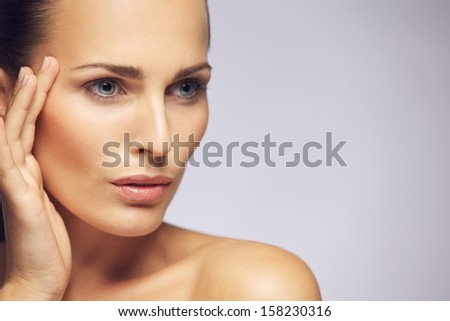 Closeup portrait of pretty young female touching smooth and healthy skin of her face and looking away against gray background. Beautiful woman model with perfect skin. - stock photo