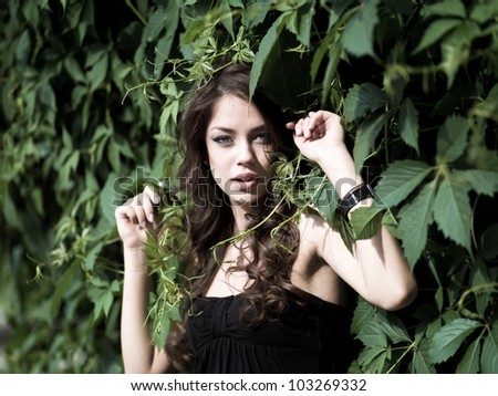 Closeup portrait of pretty young girl among leaves in a park - Outdoor