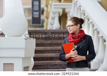 Closeup portrait of pretty young student girl holding exercise books and folder - stock photo