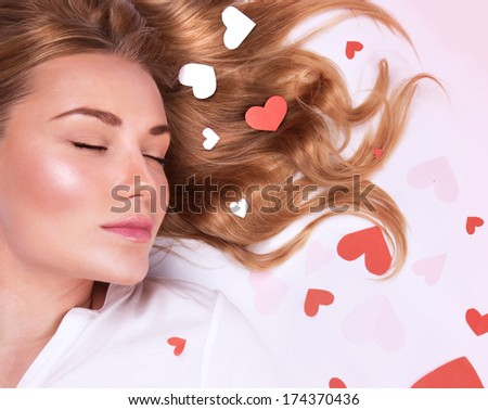 Closeup portrait of romantic fashion model lying down with closed eyes, beautiful long hair with red and white heart on it, Valentine day holiday - stock photo