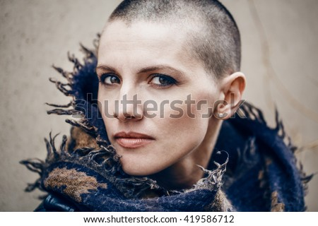 Closeup portrait of sad beautiful Caucasian white young bald girl woman with shaved hair head in leather jacket and scarf shawl, spiritual mood state of mind, conceptual art, peaceful warrior - stock photo