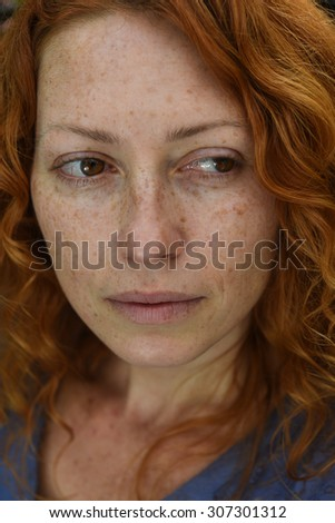 closeup portrait of sad redhead woman without makeup looking back - stock photo