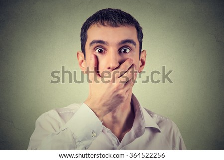 Closeup portrait of scared young man with hand over his mouth, stunned and speechless, isolated on gray wall background. Human face expression emotion feelings  - stock photo