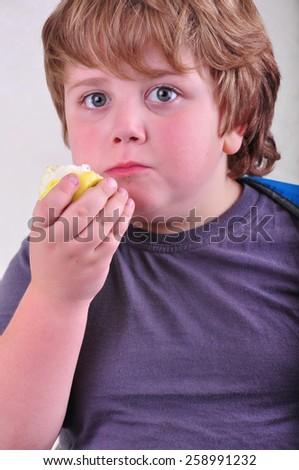 closeup portrait of schoolboy eating apple - stock photo