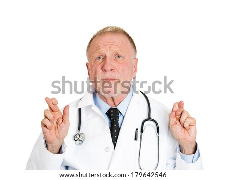 Closeup portrait of senior health care professional, old male doctor, crossing his fingers, hoping for best patient outcome, isolated on white background. Human face expressions, emotions, reaction - stock photo