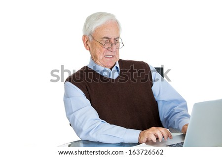 Closeup portrait of serious frustrated senior mature elderly gentleman in brown sweater typing away on his laptop, isolated on white background, space to left.  Technology gap with aging - stock photo