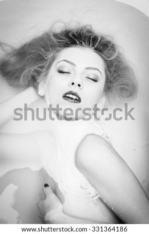 Closeup portrait of sexy beautiful female in luxury spa with silk skin having fun laying in clear water bath. Black and white photography - stock photo