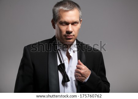 Closeup portrait of sexy man in suit with untied bow tie