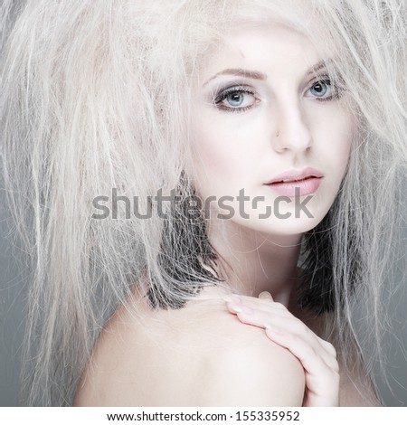 Closeup portrait of sexy whiteheaded young woman with beautiful blue eyes on grey background - stock photo
