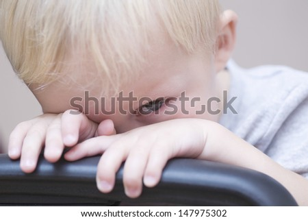 Closeup portrait of shy baby boy peeking over chair on colored background - stock photo