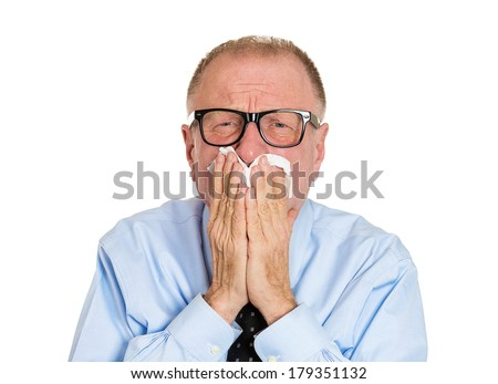 Closeup portrait of sick old man, senior worker, executive with allergy, germs cold, blowing his nose with kleenex, looking miserable unwell, isolated on white background. Flu winter season, vaccine - stock photo