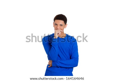 Closeup portrait of skeptical young man placing chin on hand in blue shirt looking at you camera gesture, isolated on white background, copy space to left. Negative human emotion facial expressions - stock photo