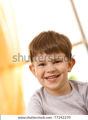 Closeup portrait of small boy laughing, looking at camera.? - stock photo
