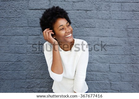 Closeup portrait of smiling african young woman looking away against grey wall