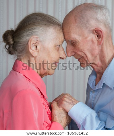 Closeup portrait of smiling elderly couple Old people holding hands. Concept of marital fidelity, providing for old age, reliability, care for the elderly, love confession  - stock photo