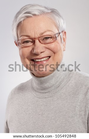 Closeup portrait of smiling elderly lady in grey sweater and glasses.