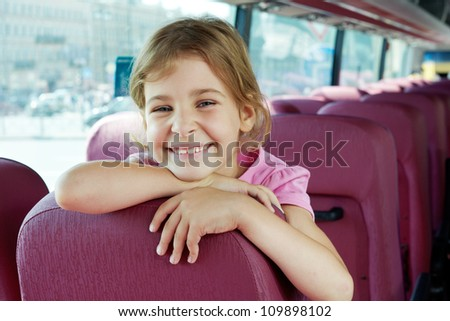 Closeup portrait of smiling girl on bus seat - stock photo