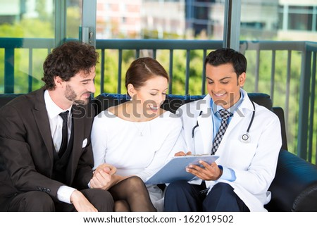 Closeup portrait of smiling health care professional or doctor or nurse showing explaining testing results to happy young successful couple on black couch in office, isolated on city urban background - stock photo