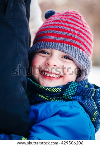 Closeup portrait of smiling laughing Caucasian toddler boy child in winter clothes hugging his mother parent outside, winter fun, lifestyle concept, beautiful smile, natural emotional face expression - stock photo