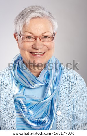 Closeup portrait of smiling mature woman in blue. - stock photo