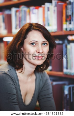 Closeup portrait of smiling middle age mature woman student in library looking in camera, teacher  librarian profession, back to school concept - stock photo