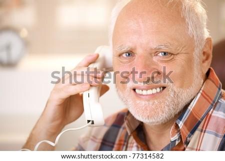 Closeup portrait of smiling senior man using landline phone, looking at camera.? - stock photo