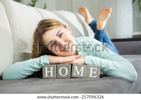 "Closeup portrait of smiling woman lying on word ""home"" spelled by letters on bricks - stock photo"