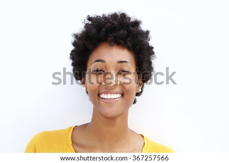 Closeup portrait of smiling young black woman against white background  - stock photo